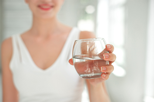 Nitrates: chlorine use in drinking water: women in whit tank holding glass of water
